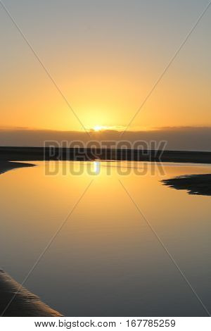 Sun rise over perfectly still waters at the beach