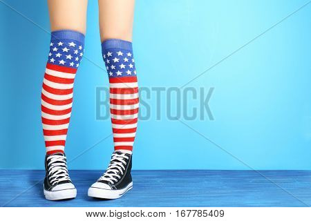 Woman in striped stockings on color background