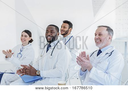 Great report. Satisfied doctors are clapping hands and smiling. They are sitting at clinic