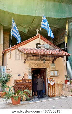 ATHENS MAR 27 2016: Greek street with people entering the church door with blue striped flags above in residential area of Athens