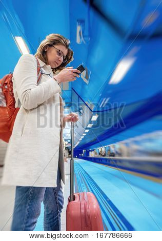 Blue tone background traveler woman in elegant white coat waiting for train and surfing the mobile internet on a smartphone in the Athens subway station with travel luggage bag