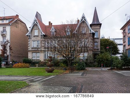 Beautiful French house in the city of Schiltiheim on a rainy fall day with beautiful timbered decorations and tree in front of the house
