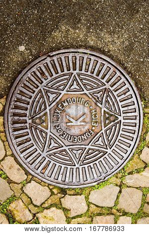 Fonderie de Luxembourg translating as Luxembourg Foundry - manhole cover surrounded by old cobblestone