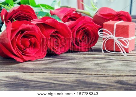 gift and red roses on a wooden brown background