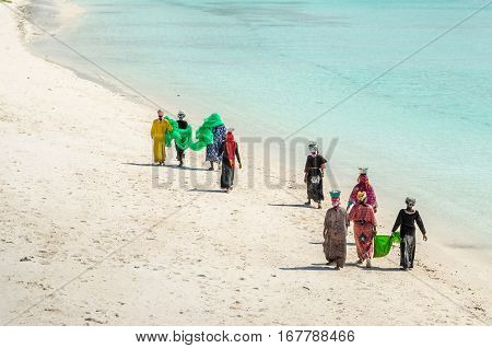 Zanzibar Tanzania - November 4 2016: Women with colorful clothes walking along the Nungwi beach carrying their net and pots with small fishes on their head. After a couple of hours of fishing they take home just a full pot of small fishes.