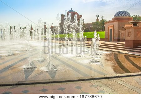 Splash of water outside of Emirates Palace a luxurious and most expensive 7 star hotel in Abu Dhabi. Abu Dhabi is a famous travel destination in United Arab Emirates. Luxury travel concept.
