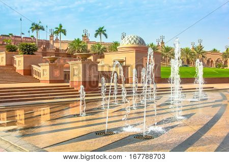 Garden and fountains outdoors of Emirates Palace a luxurious and most expensive 7 star hotel in Abu Dhabi. Abu Dhabi is a famous travel destination in UAE. Luxury travel in Middle East concept.