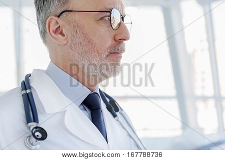 Pensive general practitioner is analyzing human health. He is standing in while coat with stethoscope