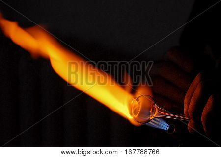"Free-blowing is a glass blowing technique now mainly used for artistic purposes. It involves blowing puffs of air into a molten blob of glass called a '""gather"" which is affixed to one end of the blowpipe. This picture shows the hand of a g poster"