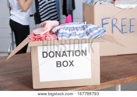 Donation boxes with clothing on wooden table