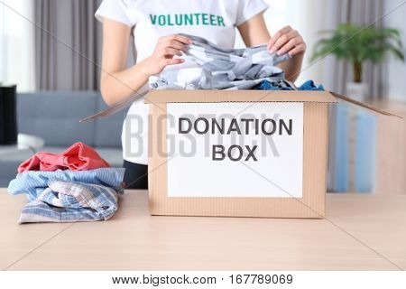 Female volunteer putting clothes in donation box