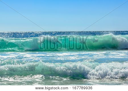 Big waves in Noordhoek Beach in a sunny day. Surfing in Cape Town, South Africa. Atlantic coast, Table Mountain National Park. Extreme sports leisure concept. Powerful waves background. Copy space.
