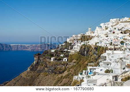 View of Thira the greek town on the island Santorini with its traditional white houses churches with their typical blue painted domes and the Aegean Sea