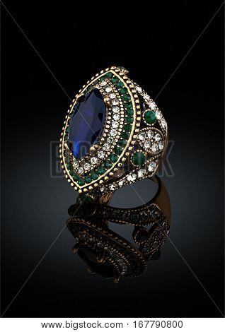 Golden ring with gems and diamonds on black