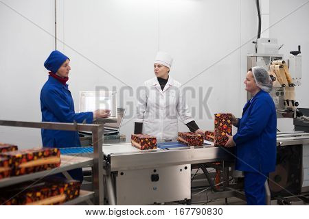 SHUCHIN BELARUS - JANUARY 26 2015. Women engaged in the packaging of cheese on a cheese factory.