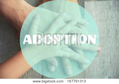 Adoption concept. Family hands on wooden background