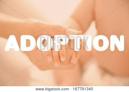Adoption concept. Mother holding hand of baby