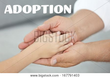 Adoption concept. Grandfather holding hand of grandchild