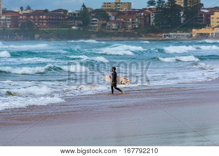 Sydney Australia - August 7 2016: Male surfer on Elouera beach on early morning
