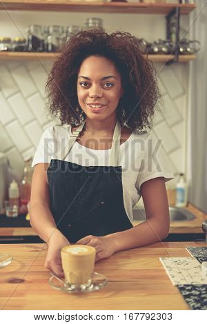 Waist up portrait of glad woman holding out cup of latte while standing at bar counter. Various spice and herbs jars are behind her