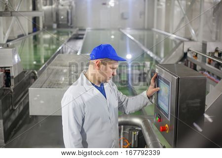 SHUCHIN BELARUS - JANUARY 26 2015. man worker operating production line at the cheese factory.