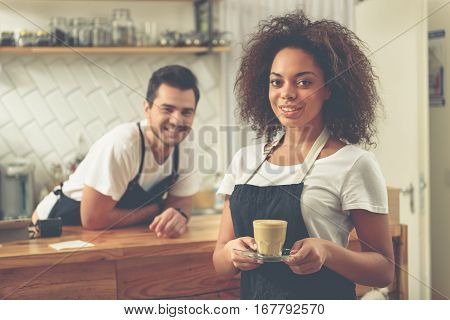 Focus on waist up pretty unconcerned woman standing with cup of tasty latte. Smiling barista leaning on worktop near cash register
