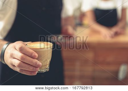 Focus on service man caring cup of coffee to client. Bartender standing behind vending table in comfortable cafeteria