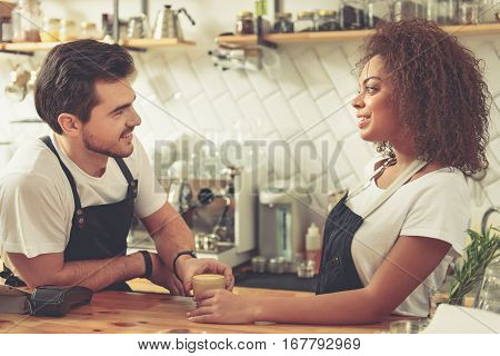 Smiling man and happy woman speaking in comfortable cafeteria. Coffee house partners looking at each other during conversation while keeping one glass of latte