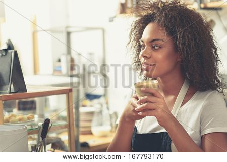 Dreamed woman holding glass of tasty milk coffee while standing near shelf with cakes confectionary shop