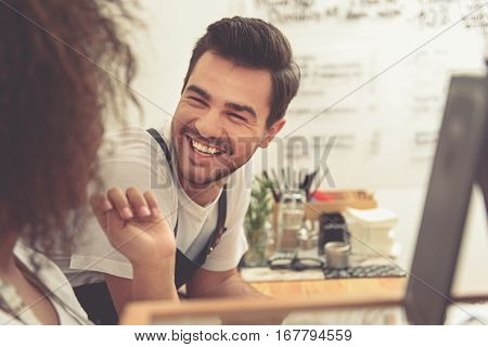 laughing attractive man speaking with woman while leaning on worktop in sunny cafe