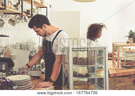 Serene male barista making delicious americano with coffee mill in comfortable cafe. Happy woman standing at counter while wiping counter
