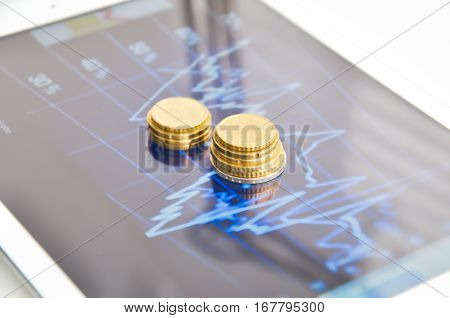 Digital tablet with financial graph and stack of coins on display