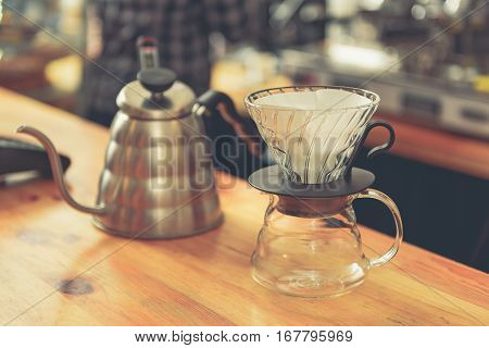 Focus on close up teapot and glass cups are on wooden worktop in coffee house