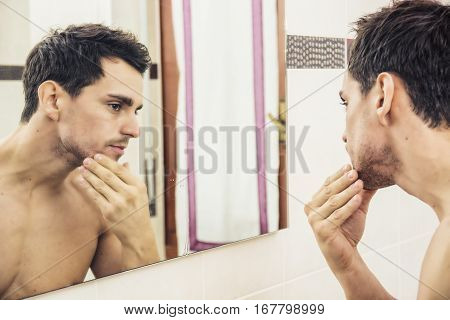 Shirtless handsome young man examining his stubble in bathroom mirror in the morning