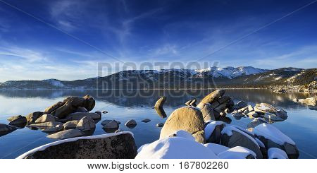 Winter shot of Lake Tahoe with snow on rocks and mountains. Sand Harbor Nevada