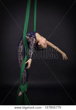 Girl's aerial acrobatics in the paintings - dark background. Studio photography of circus performers