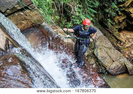 Beaufort,Sabah,Malaysia-Jan 28,2017:girl to abseil down a waterfall in Beaufort,Sabah,Borneo.Waterfall Abseiling activity adventure getting famous in Sabah,Malaysia.