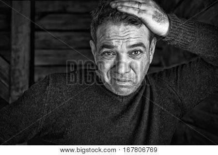 Sad man portrait. He clutched at his head. Black and white