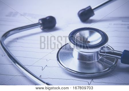 Stethoscope on electrocardiogram lying at the desk.