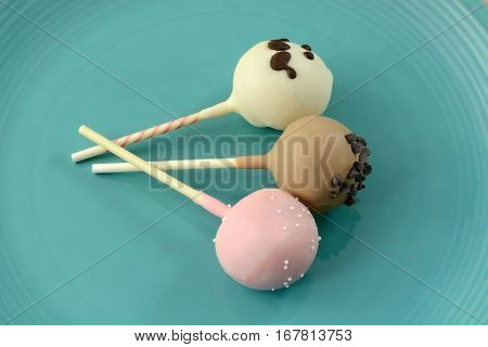 Three different cake pop popsicles on blue plate