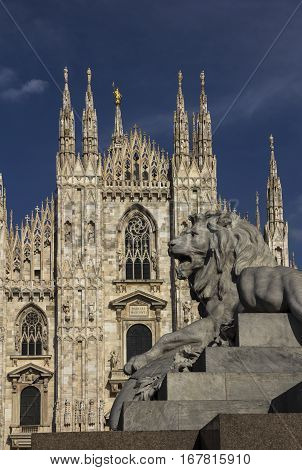 A lion figure on a side of Vittorio Emanuele II equestrian statue pedestal in front of Duomo (Cathedral) on Piazza del Duomo of Milan, Italy