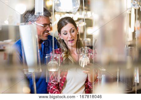 Couple, woman and man, woman and man, in electrical goods department of hardware store looking for lamps