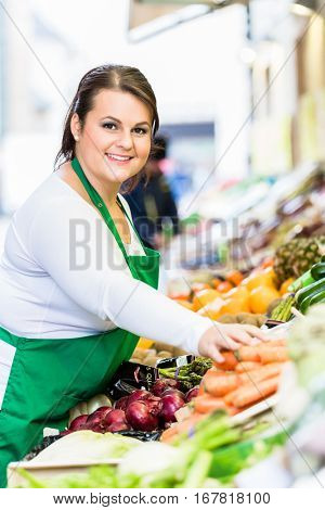 Saleswoman with fruit and vegetables at famers market