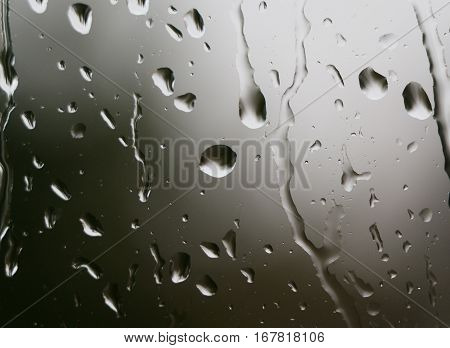 Rain on windowpane, drops running down, closeup