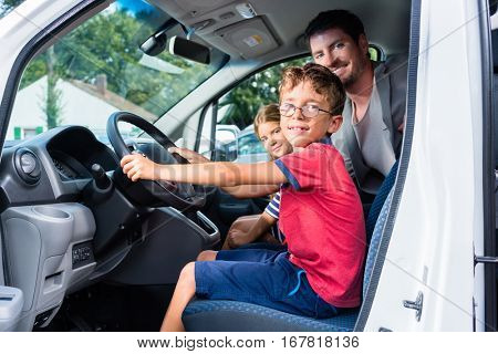 Family having test drive of new car at dealership, young son on the steering wheel