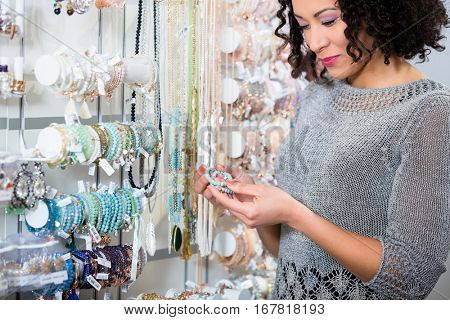 Young woman looking at trinket in shop