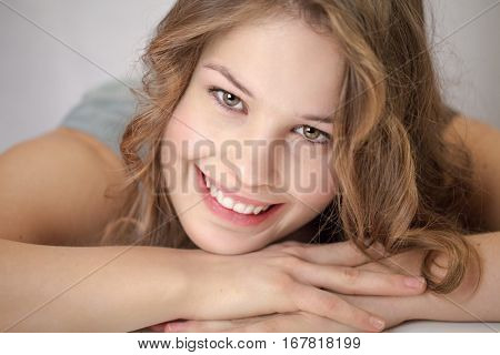 Pretty young woman is smiling at camera with chin on hands, looking up,