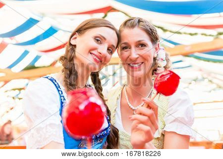Two friends wearing dirndl and holding candy apples in a beer tent at Regensburger Dult