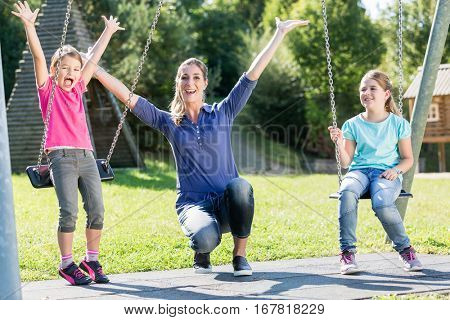 Family with two girls and mother on playground swing