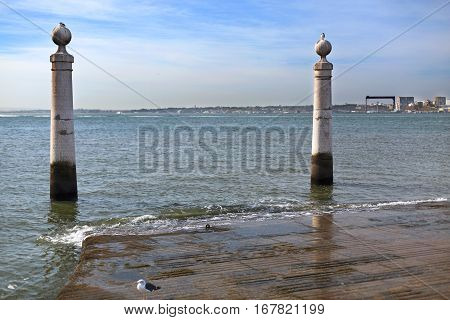 LISBON, PORTUGAL - September 26, 2016: Cais das Colunas is a marble flight of steps flanked by two water stained marble columns which runs gently into the Tagus River in downtown Lisbon Portugal